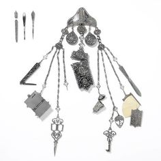 A chatelaine which was displayed at the Great Exhibition of 1851. Before the 1850s pockets were uncommon in female clothing and so women used chatelaines as a fashionable, decorative means of carrying small and useful items. The chatelaine would be hung from a belt and, through a series of clips and chains, contain a variety of objects such as scissors, keys, scent bottles, penknives, tweezers, writing pads and letter openers. Antique Jewelry, Vintage Jewelry, Vintage Purses, Historical Clothing, Female Clothing, Antique Sewing Machines, Crystal Palace, Fashion History, Vintage Sewing