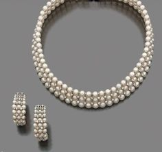 Collier en or gris, en trois rangs de perles de culture piquées de petits diamants. Fermoir en