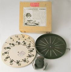 """""""Gramophone Cinema"""" (1920s). An illustrated disk sits on the top of a record and a disk with slots rides on a wooden spindle with rollers over it. As the record turns the animation can be seen through the slits. The cards include Felix the Cat and a Charlie Chaplan-esque tramp."""