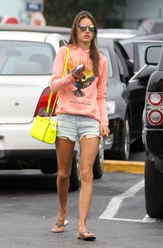 Alessandra Ambrosio Street Style - Alessandra Ambrosio punched up her denim cutoffs with a bright coral sweatshirt, a neon yellow Michael Michael Kors bag, and mirrored sunglasses in LA.