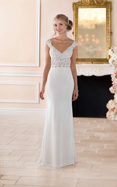 This cap sleeve column wedding dress from Stella York is a fashion forward statement piece! Lace and crepe chiffon over Imperial crepe create a sleek shape that feels like a breath of fresh air. The stunning lace on the illusion bodice flows down onto the crepe skirt creating an asymmetrical detail that is truly unique. The mock keyhole back pairs with a substantial, yet light, train for an elegant exit down the aisle. Finishing the look are lace cap sleeves that stem from a deep v-neckline.