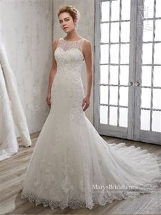 Mermaid tulle bridal gown with bateau neck line, pearl and beading details, re-embroidered lace appliques, scallop hem line, and cathedral train.