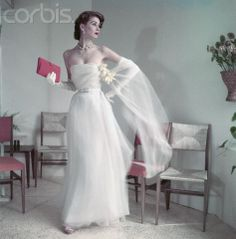 Model wearing white strapless ballgown with long gloves, stole with daffodil corsage, and a red clutch