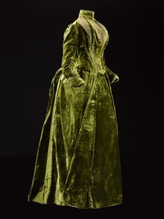 Woman's dress, one of a two part ensemble, in dark green silk velvet, fastening at the front with a standing collar with lapels, bodice front and cuffs trimmed with dark green ribbed silk, full-length sleeves and the skirt shaped for a bustle at the back with a large self-material bow: British, Scottish, Edinburgh, by Gowan and Strachan, c.1885 - 1888  Museum reference K.2014.25.1