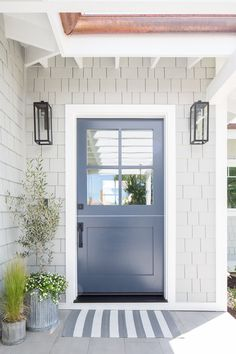 Gray beach home features a blue front door with windows styled with a striped do.Gray beach home features a blue front door with windows styled with a striped doormat, galvanized planters and gray shingles illuminated Gray House Exterior, Beach House Exterior, Front Doors With Windows, Exterior Doors, House Exterior, Beach House Colors, House Paint Exterior, Navy Front Door, Cottage Exterior