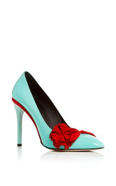 This pump by **Oscar de la Renta** is rendered in sea foam patent leather and features a floral embellishment on the toe.