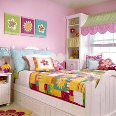 Colorful Quilt  Bubble-gum pink walls glow behind brightly colored bedding, pillows, and wall art. Over the window, a unique awning-style valance adds color and dimension.