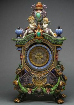 FINE CONTINENTAL POLYCHROMED MAJOLICA RENAISSANCE INSPIRED MANTEL CLOCK circa 1870, unmarked, surmounted by two putti dotted with foliage and hung with garlands, the base with a bearded satyr mask flanked by acanthus and hung with fruited festoons, on four shaped legs ending in paws.