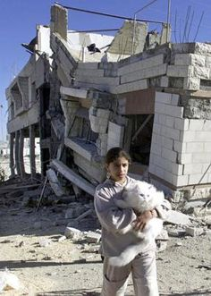 Palestinian girl in front of a demolished home in Balata refugee camp, 2002.