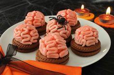 Dolcetti decorati a forma di cervello: assolutamente deliziosi e orripilanti al tempo stesso. ;) Perfetti per Halloween! Ai bambini faranno tanto ridere, e sono così facili che possiamo prepararli tutti insieme.  Ingredienti: biscotti al cioccolato, Nutella, panna per dolci da montare, 2 cucchiai di zucchero a velo, colorante alimentare rosso. Incolliamo i biscotti due a due spalmandovi la Nutella al centro. Montiamo la panna con lo zucchero a velo e 3 gocce di colorante alimentare rosso o…