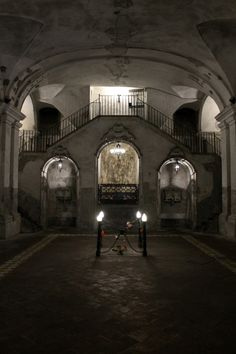 """The crypt of the Church of Santa Maria delle Anime in Naples. In past centuries there developed here a cult of the dead. When remains were disinterred from the common grave in the floor (marked by the lights), the skulls were stacked in side chapels; devotees paid visits to them, cleaned them, and, in a way, """"adopted"""" them, even giving the skulls back their """"living"""" names (revealed to their caretakers in dreams). The practice was abolished in the 20th century, only to..."""
