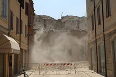Smoke rises from a building that collapsed after a earthquake in Mirandola