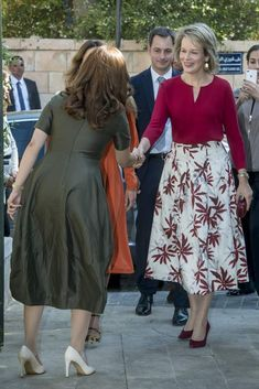 Reina Matilde de Bélgica Acto: Visita a la fundación Jordan River (Jordania). Fecha: 25 de octubre de 2016. `Look´: La soberana belga escogió para una de sus visitas dentro de su viaje oficial a Jordania, una falda de vuelo en color blanco con estampado burdeos y una blusa con detalle metálico a juego. Completan su 'look' unos zapatos de salón de ante, un pequeño 'clutch' y unos pendientes dorados.