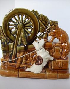 Genuine vintage McCoy USA planter with Spinning Wheel and a cute little terrier on a gold cord leash. He's barking at a cat, seen in the upper right hand corner of the piece. The back is a planter spa