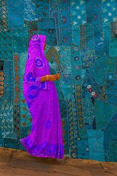 Woman walking past a tapestry, jodphur, rajasthan