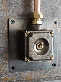 Reclaimed industrial light switch mounted onto 16 gauge steel plate which has been gently heated on a kitchen hob, bringing out some fabulous colours and blending in with the distressed copper panel wall paper. Finished off with dummy 15mm copper pipe conduit.