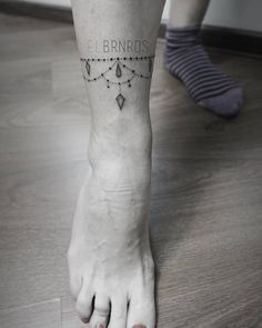 Fine line style ankle band tattoo.