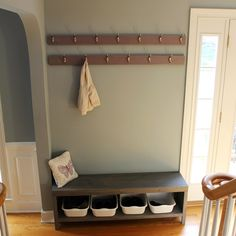 Making our foyer more functional with a many hooked coat rack and bench with shoe storage