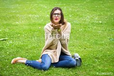 Beautiful girl sending a kiss sitting on the grass