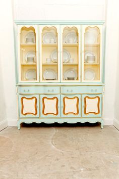 A vintage china cabinet painted in soft colors and accented with gold could be used in a variety of design styles from Shabby Chic to Hollywood Regency.