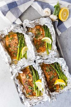 Four salmon fillets on a baking tray in foil with asparagus and lemon wedges with garlic and lemon in the background Baked Salmon And Asparagus, Lemon Garlic Salmon, Baked Salmon Recipes, Asparagus Recipe, Seafood Recipes, Dinner Recipes, Fresh Asparagus, Foil Packet Meals, Salmon Foil Packets Grill
