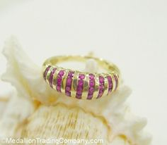 14k .60 Carat Channel Set Ruby Stripe Dome Shrimp Band Ring Size 6 -- $279.95 MedallionTradingCompany.com .   Ring Size: 6,  resizeable up or down 1/2 a size.   Width: Approximately 7mm at the widest point in the dome   Total Weight: 3.4 grams    Markings: 14k,  unidentified maker's mark   Metal: Band is 14k solid gold, marked and tested   Stones:  (39) round cut natural ruby gemstones approximately .60 carats total.  The stones are nice color and clarity, and the gemstones are uniform