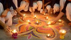 Indian schoolgirls light candles as they sit near a rangoli (a decorative design with sacred overtones) made out of colored powder during a pre-Diwali celebration at a school in Amritsar on November (Narinder Nanu/AFP/Getty Images) Diwali Celebration, Celebration Around The World, Hindu Festivals, Indian Festivals, Indian Festival Of Lights, Hindu New Year, Diwali Festival, Diwali Gifts, Holidays Around The World