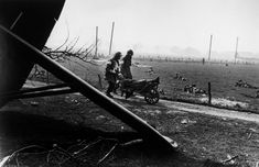 Near Wesel. March 24th, 1945. Medics evacuate an injured American paratrooper. In the foreground: the wreckage of an allied glider//Robert Capa
