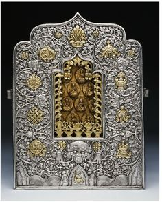 A twentieth-century silver and clay Tibetan travelling amulet box; the protective deities, the 21 Taras are at the centre; the silver front is adorned with the wish-fulfilling jewel at the apex, Buddism's Eight Auspicious Emblems at the sides and with a protective monster mask at the bottom. (Victoria & Albert Museum)