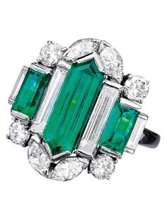 Oscar Heyman - An Art Deco diamond and emerald ring. The ring centring a double bullet cut Colombian emerald flanked by unusual long baguette diamonds, matching emerald cut emeralds, and further accented top and bottom with marquis and European cut diamonds.