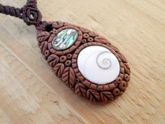 A beautiful hand sculptured pendant of polymer clay with a spiritual Shiva Eye Shell and Abalone knotted with dark brown wax thread in a micro macrame necklace
