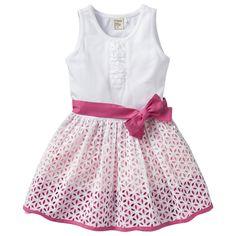 De jurk heeft een tricot bovenstukje, een roze sierlint in de taille en randje roeseltjes bij de hals. De geplooide onderrok is roze / zalm en daaroverheen zit een witte broderie rok.