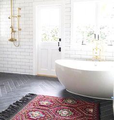 Herringbone tile  floor free standing white tub and subway tile