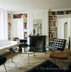 /\ /\ . Frédéric Méchiche . Paris Apartment . Library . 19th century wall panelling and bare floorboards rescued from a salvage yard provide a setting for 20th century furniture and Barcelona chairs.