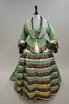 A green watered silk formal gown, circa 1865, the lightly padded bodice trimmed with cream and black lace and bows, the horizontally banded skirt with matching waist-sash.