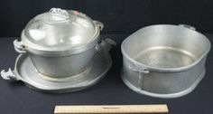 GUARDIAN SERVICE ALUMINUM COOKWARE INCLUDING A POT WITH GLASS LID, A POT WITHOUT A LID, LARGE ROASTING POT, AND ROUND PLATTER.