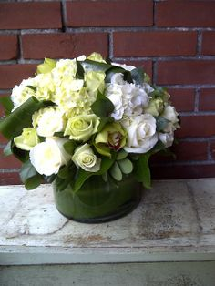 Green and white roses and cymbidium orchids highlight this beautiful flower arrangement. nspired... Naturally