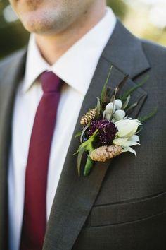 The groomsmen in dark gray suits and bordeaux red wedding ties.