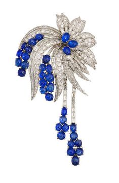 A Sapphire and Diamond Brooch -- circa 1950 -- designed as a spray of round brilliant and baguette-cut diamonds, accentuated by oval-shaped cabochon sapphire clusters; estimated total diamond weight: 9.00 carats; mounted in fourteen karat white gold