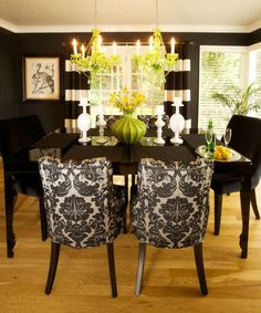 Lighter colors w/ red chandeliers & vase, printed wallpaper, dark stained wood table.