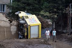 Volunteers walk past an overturned truck, after Sunday's flooding, in Tbilisi, Georgia, June 15, 2015. AP Photo/Pavel Golovkin