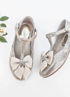 In a luxe, beautiful silver hue with metallic and jeweled accents, these pretty t-strap shoes will quickly become her favorite. Comes with a matching clip!