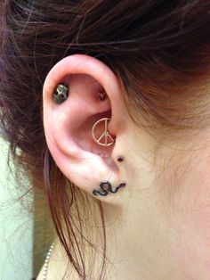 Custom peace sign jewelry in a daith piercing. Designed by Chris Jennell, built … Custom peace sign jewelry in a daith piercing. Designed by Chris Jennell, built by Body Vision Los Angeles. Tragus Piercings, Piercing Tattoo, Piercing No Lóbulo, Daith Piercing Schmuck, Piercings Corps, Daith Rings, Body Piercings, Smiley Piercing, Gauges