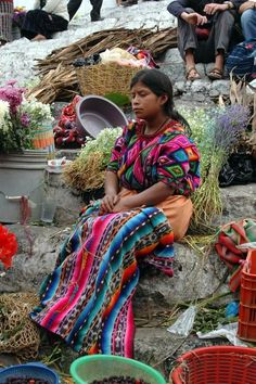 She seems lost in thought. I love her colorful clothing. Guatemala.
