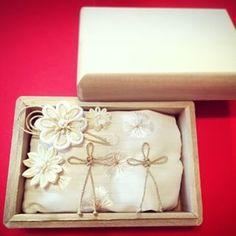 「ざっくり!!リングピローの作り方」 材料:木の箱(東急ハンズ)、好きな布(写真は半襟)、好きな紐、パール、ペップ、ちりめん布 ①事前準備としてYouTubeでつまみ細工職人さんの動画をめっちゃみる。作ってみる笑 ②箱の大きさに合わせてまくらを作る。 ③お花の中央にボンドをつけてペップやパールをのせます。 ④飾り紐の動画をめっちゃみる。→作ってみる。 ⑤できた飾り紐を縫い付ける。 完成!