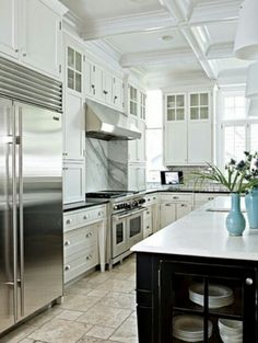 A timeless white kitchen features tile floors, marble backslashes and furniture like legs to the cabinet bases.