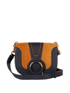 See By Chloé's Hana cross-body bag has a traditional equestrian-inspired air thanks to the matte gold-tone metal hardware, woven trim, and curved saddle shape. The contrasting panels of tan suede and navy leather lend a luxuriously tactile feel. Extend the adjustable strap to sling it across the body for day, and then remove it to style as a clutch after dark.