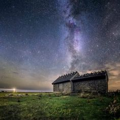 A little fishing cottage on the Swedish coast beneath the vast Milky Way.