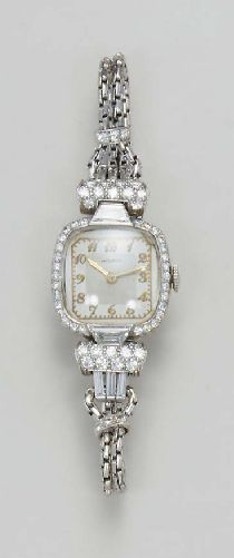 AN ART DECO PLATINUM AND DIAMOND WRISTWATCH, BY MOVADO Of nickel-finished lever movement, 17 jewels, the white square dial, with applied gold Arabic numerals and hands, to the circular-cut diamond surround and shoulders, enhanced by fancy and baguette-cut diamonds, to the twin link chain, accented by circular-cut diamonds, mounted in platinum, 5 ins. Movement signed Movado Switzerland
