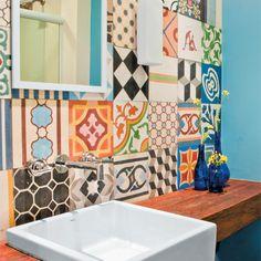 """Para receber. No lavabo, a parede do espelho foi revestida de 70 ladrilhos hidráulicos de estampas diferentes (Dalle Piagge). A bancada de madeira (1,40 x 0,30 m, da Móveis Planejados Fartura) compõe bem com a cuba (Deca) de encaixe, de linhas retas e modernas. """"A proposta foi deixar bonitas as áreas por onde os amigos circulam"""", afrma Luiza."""